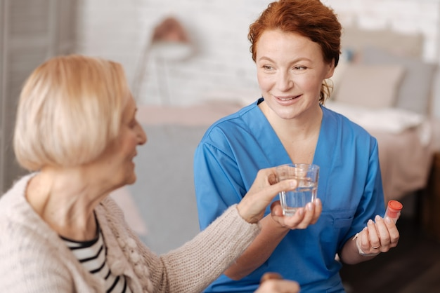 Portion quotidienne. spécialiste privé de premier plan qualifié prenant soin d'une dame âgée et lui donnant un verre d'eau pendant qu'elle suit un traitement médical