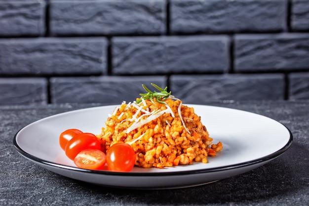 Une portion de risotto bolognaise de boeuf haché saupoudré de parmesan râpé sur une assiette avec un mur de briques à l'arrière-plan, cuisine italienne, gros plan