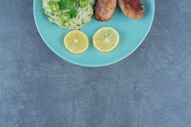 Portion de riz avec cuisses de poulet sur plaque bleue.