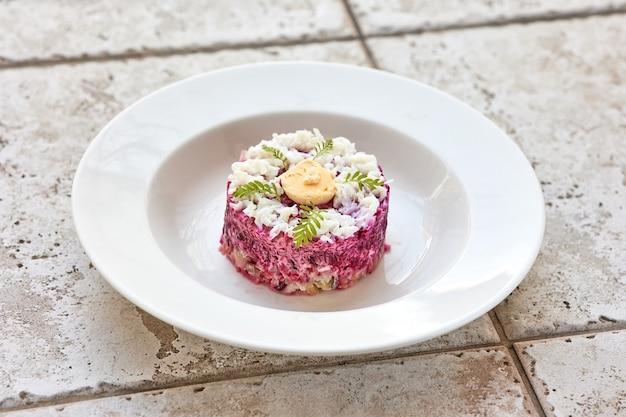 Portion de salade de hareng et de betterave sur plaque blanche