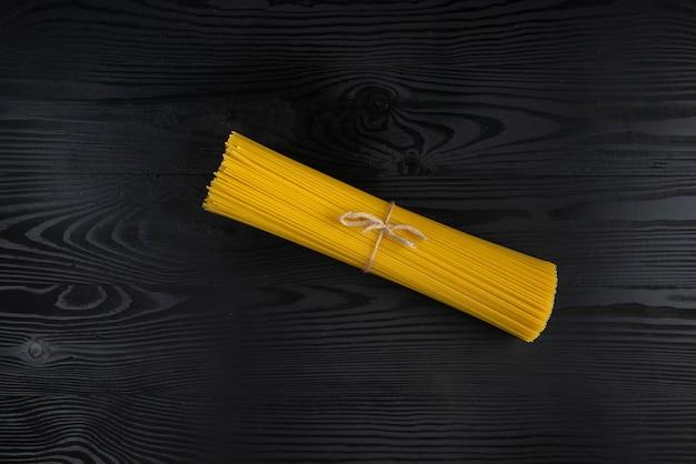Une portion de spaghettis crus sur la table en bois