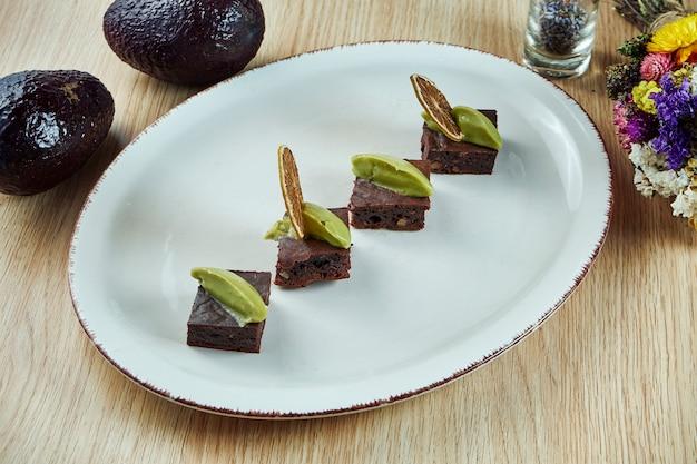 Portion de tarte au brownie avec de la pâte d'avocat sur une plaque blanche. dessert sucré pour le déjeuner. vue sur la nourriture savoureuse