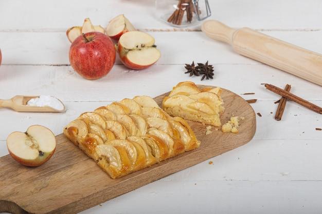 Portion de tarte aux pommes sur une planche à découper en bois avec divers ingrédients. bâtons de cannelle et sucre lustré.