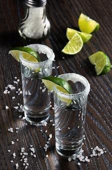 Portion de tequila, encadrée d'un bord de sel avec tranche de citron vert dans de grands verres à liqueur