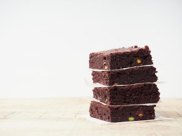 Portions de brownie carrés empilés avec du papier entre eux sur une table en bois avec un fond blanc