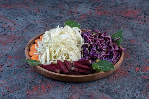 Portions de choux rouges et blancs hachés, betteraves et carottes sur un plateau sur fond de couleur sombre. photo de haute qualité