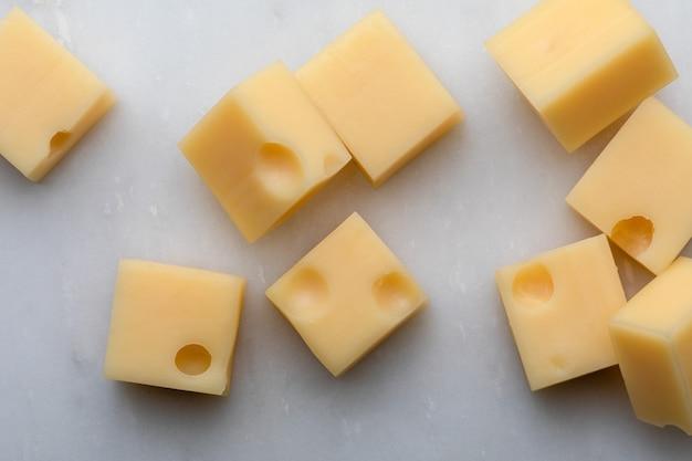 Rébus (...) Portions-cubes-fromage-suisse-emmental-grattoir-texture-trous-alveoles-fond-marbre-blanc_131238-750