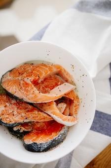 Portions de filet de saumon frais avec des herbes aromatiques et des épices dans un bol sur la table dans la cuisine