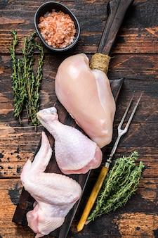 Portions de poulet cru pour la cuisson et le barbecue avec des poitrines sans peau, des pilons et des ailes.