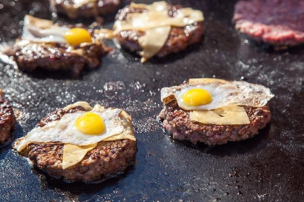 Portions de viande de boeuf avec du fromage et des œufs grillés sur la cuisinière, préparation du concept de hamburgers