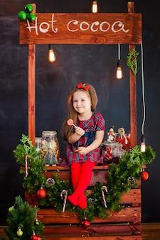 Le portrai de jolie petite fille près de noël decoratoins avec lillypop