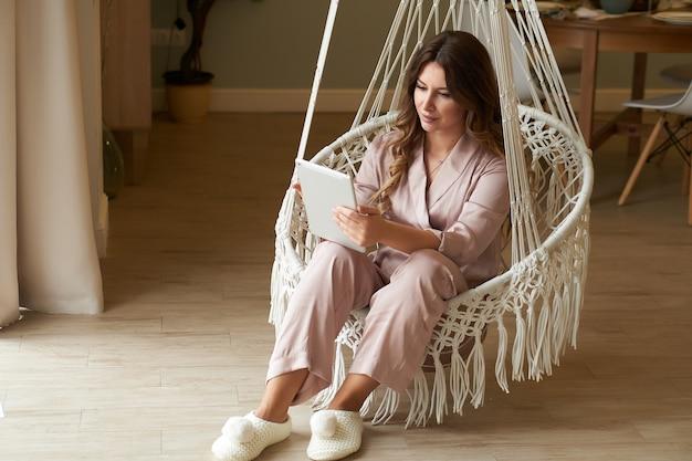 Portrair de la belle jeune femme en pyjama à la maison dans un fauteuil doux fonctionne sur la tablette