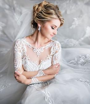 Portrair de mariée blonde rêveuse posant dans une chambre de luxe avant la cérémonie
