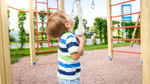 Portrait de 3 ans jouant sur le terrain de jeu et essayant de grimper sur la grande corde du parc