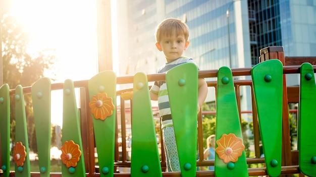 Portrait de 3 ans tout-petit garçon debout sur le pont de bois sur l'aire de jeux pour enfants au parc
