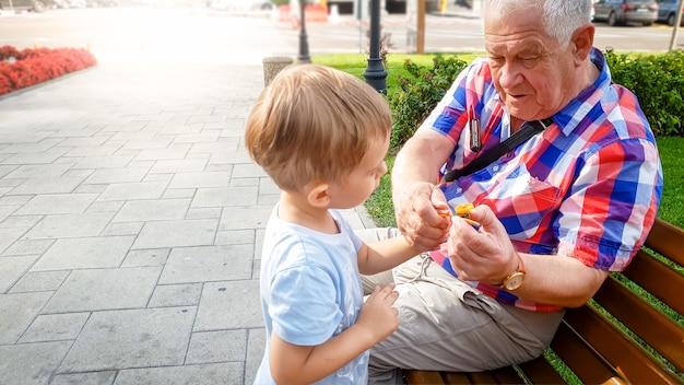 Portrait de 3 ans tout-petit garçon jouant avec son grand-père dans le parc avec un petit hélicoptère jouet en plastique