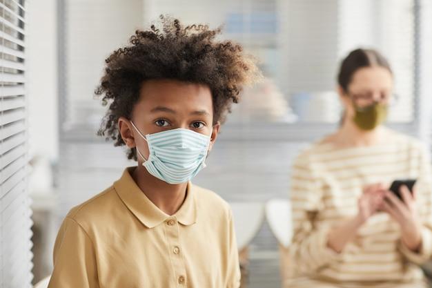 Portrait d'un adolescent afro-américain portant un masque et regardant la caméra en faisant la queue à la clinique médicale, espace pour copie