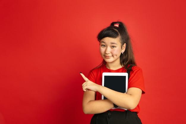 Portrait d'adolescent asiatique isolé sur espace rouge. beau modèle brune féminine dans un style décontracté