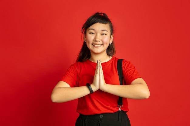 Portrait d'adolescent asiatique isolé sur espace rouge. beau modèle femme brune aux cheveux longs dans un style décontracté