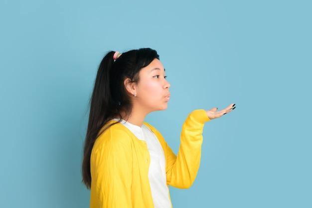 Portrait d'adolescent asiatique isolé sur fond bleu studio. beau modèle femme brune aux cheveux longs. concept d'émotions humaines, expression faciale, ventes, publicité. envoi de bisous, ça a l'air mignon.