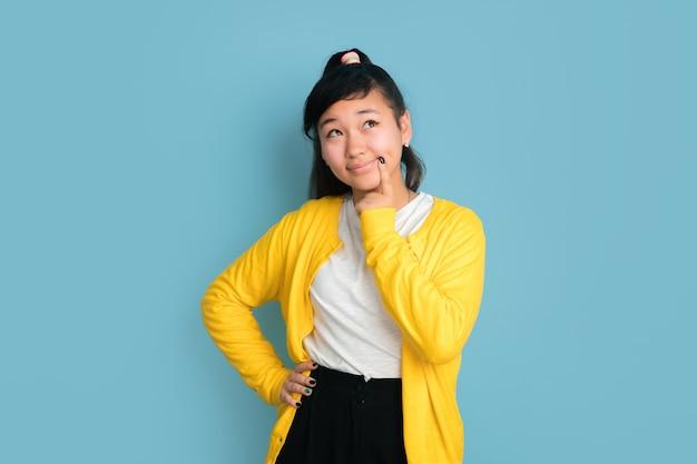 Portrait d'adolescent asiatique isolé sur fond bleu studio. beau modèle femme brune aux cheveux longs dans un style décontracté. concept d'émotions humaines, expression faciale, ventes, publicité. rêveur.