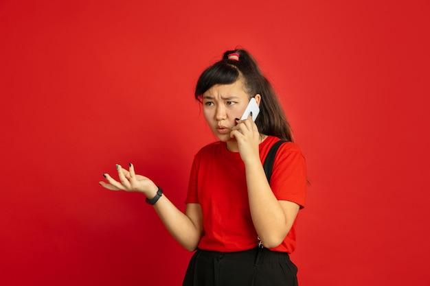 Portrait d'adolescent asiatique isolé sur fond de studio rouge. beau modèle femme brune aux cheveux longs dans un style décontracté. concept d'émotions humaines, expression faciale, ventes, publicité. parler au téléphone.
