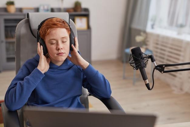 Portrait d'un adolescent aux cheveux rouges portant des écouteurs et profitant de la musique les yeux fermés tout en se relaxant ou en enregistrant un podcast, espace de copie