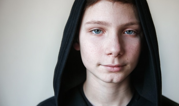 Portrait d'un adolescent calme aux yeux bleus dans un capot noir