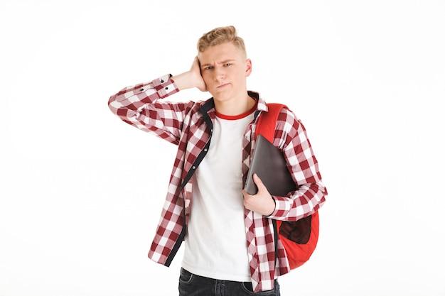 Portrait d'adolescent caucasien portant une chemise à carreaux exprimant la confusion ou un problème sur le visage et tenant un ordinateur portable argenté, isolé sur mur blanc