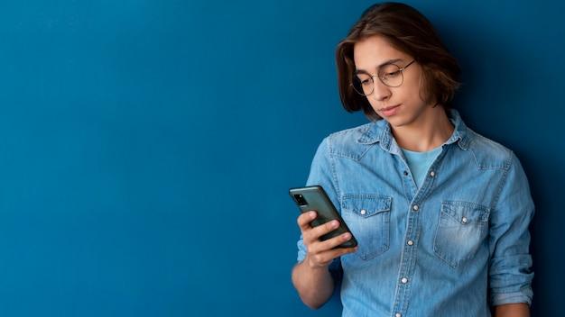 Portrait d'un adolescent cool vérifiant son téléphone