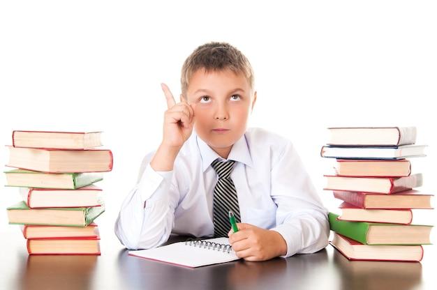 Portrait d'un adolescent garçon à l'école dans la bibliothèque près de la pile de livres. inventé, est venu l'inspiration