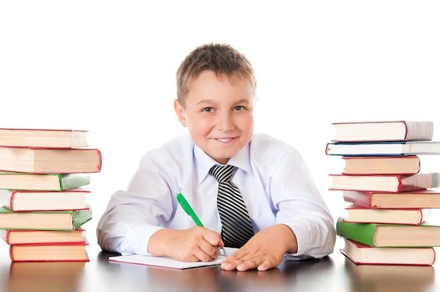 Portrait d'un adolescent garçon à l'école dans la bibliothèque près de la pile de livres