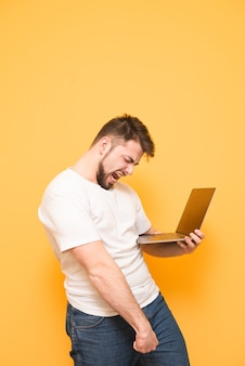Portrait d'un adolescent heureux avec une barbe debout sur jaune