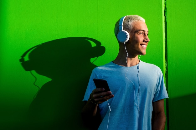 Portrait d'un adolescent ou d'un jeune homme écoutant de la musique à l'aide d'un casque - millénaire s'amusant à écouter de la musique