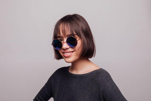 Portrait d'adolescent jolie fille à lunettes de soleil isolé.
