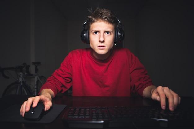 Portrait d'un adolescent joueur assis à la table et jouer à des jeux vidéo sur l'ordinateur