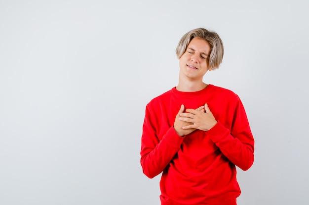 Portrait d'un adolescent avec les mains sur la poitrine tout en fermant les yeux en pull rouge et en regardant tristement la vue de face