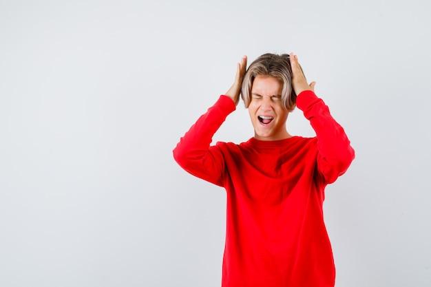 Portrait d'un adolescent avec les mains sur la tête, ouvrant la bouche en pull rouge et regardant la vue de face stressée