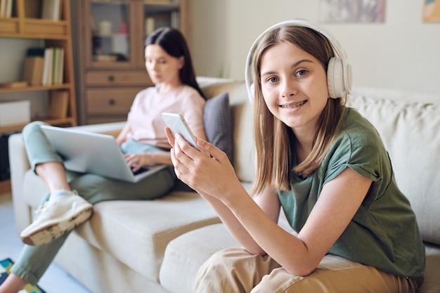 Portrait d'adolescent moderne positif dans des écouteurs sans fil à l'aide de smartphone tandis que sa mère occupée travaillant sur ordinateur portable
