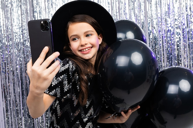 Portrait d'un adolescent narcissique sur un anniversaire prenant selfie sur un smartphone parmi les ballons d'hélium noir sur fond brillant.