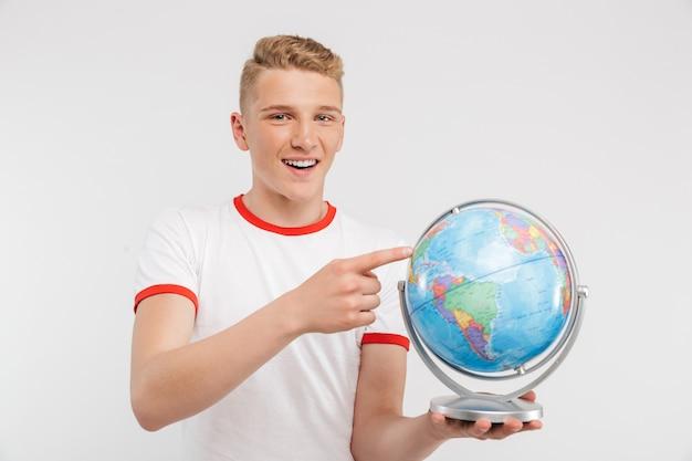 Portrait d'un adolescent pensif pointant sur un globe
