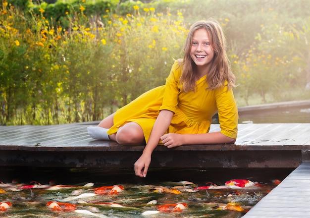 Portrait d'un adolescent sur le pont. fille nourrir les poissons dans l'étang