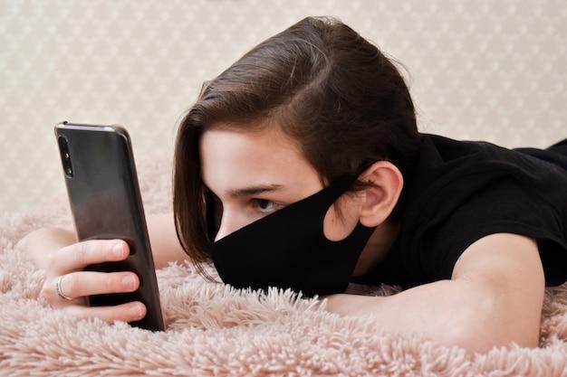Portrait d'un adolescent portant un masque médical avec un téléphone à la main sur le lit