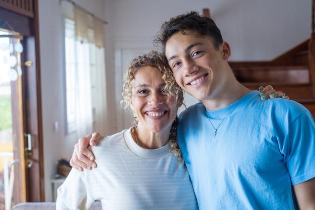 Portrait d'un adolescent reconnaissant embrasse une mère d'âge moyen souriante montre de l'amour et de l'attention, un fils adulte heureux et reconnaissant dans l'étreinte d'une maman joyeuse, profite du week-end en famille à la maison ensemble, concept de liaison