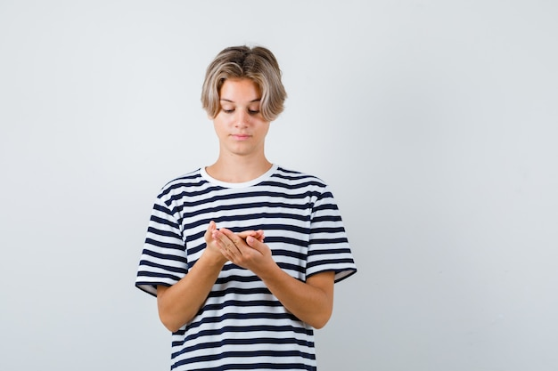 Portrait d'un adolescent regardant les paumes en t-shirt et regardant attentivement la vue de face