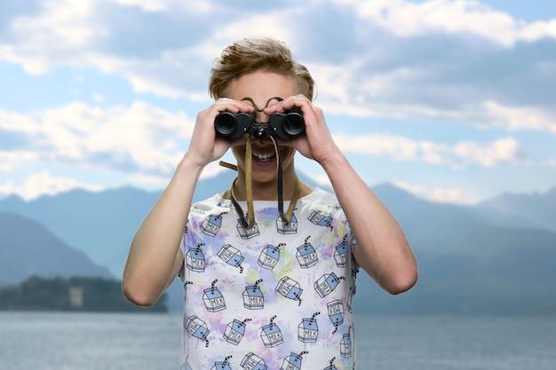 Portrait d'adolescent regarde à travers des jumelles. concept de visites de la mer. beau paysage naturel en arrière-plan.