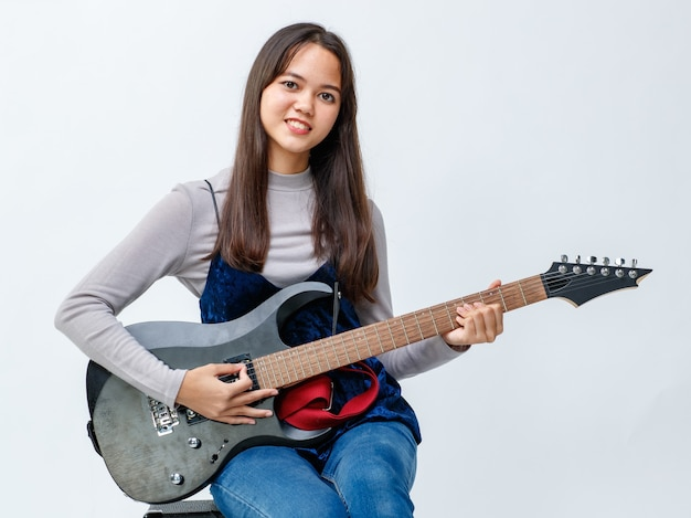 Portrait d'un adolescent thaï-turc souriant et mignon jouant de la guitare électrique. guitariste junior jouant d'un instrument tout en regardant la caméra isolée sur fond blanc. concept de passe-temps