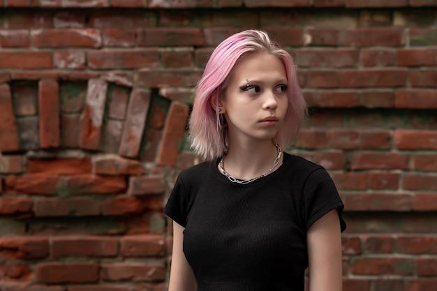 Portrait d'une adolescente aux cheveux roses sur le fond d'un vieux mur de briques