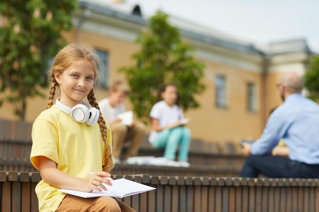 Portrait d'adolescente blonde souriant à la caméra alors qu'il était assis sur un banc à l'extérieur avec un enseignant donnant une leçon en arrière-plan, copiez l'espace