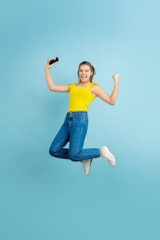 Portrait de l'adolescente caucasienne sur fond bleu. beau modèle de cheveux longs en tenue décontractée.